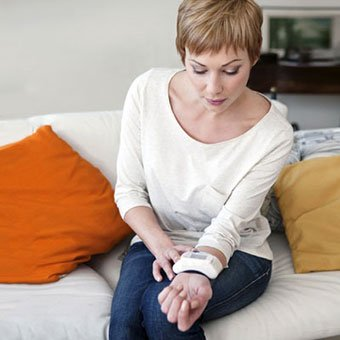 A woman checks her blood pressure at home.