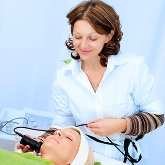A technician performs facial laser therapy.